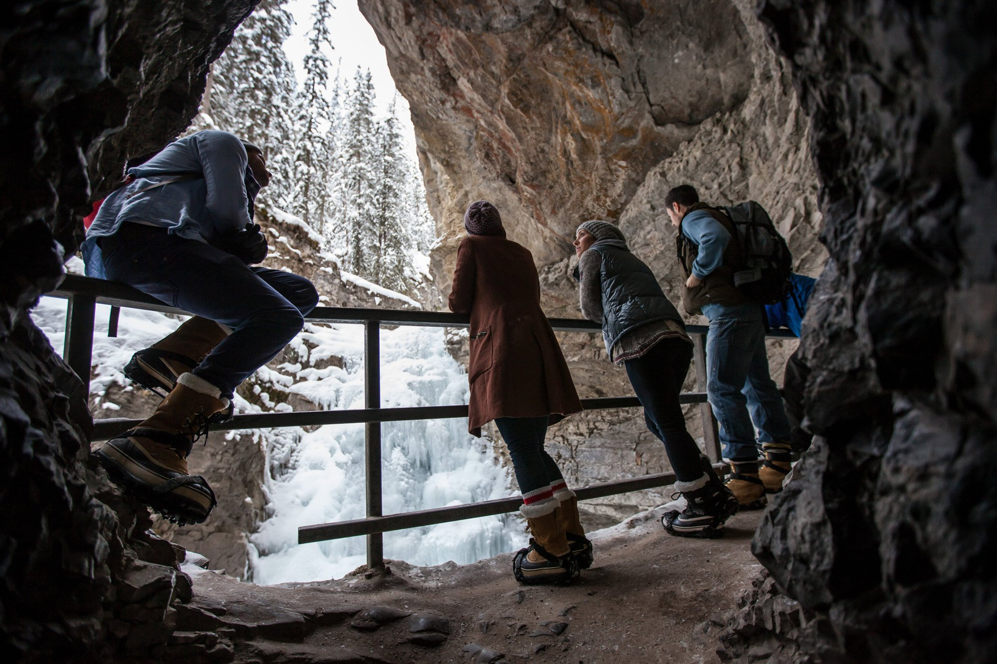 A group pauses in a cave along the Johnston Canyon ice walk in Banff, AB