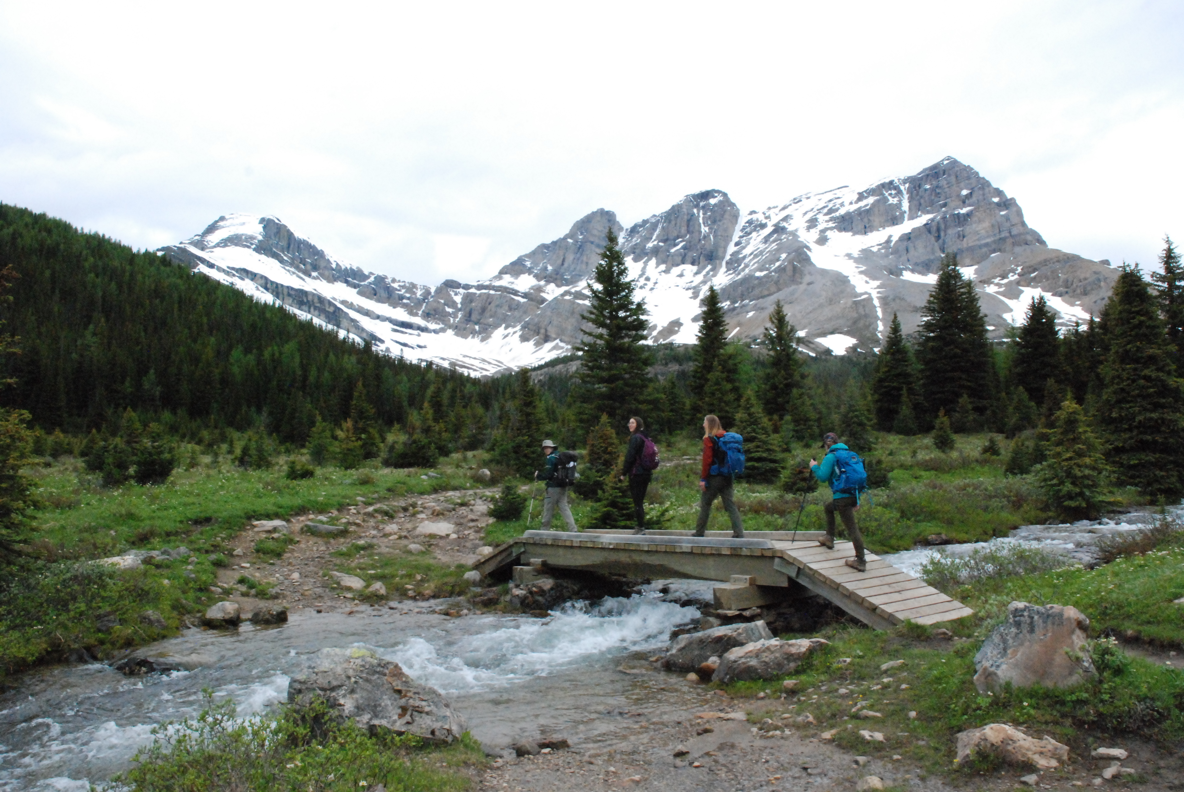 4 hikers crossing a bridge over a river with mountain in the background